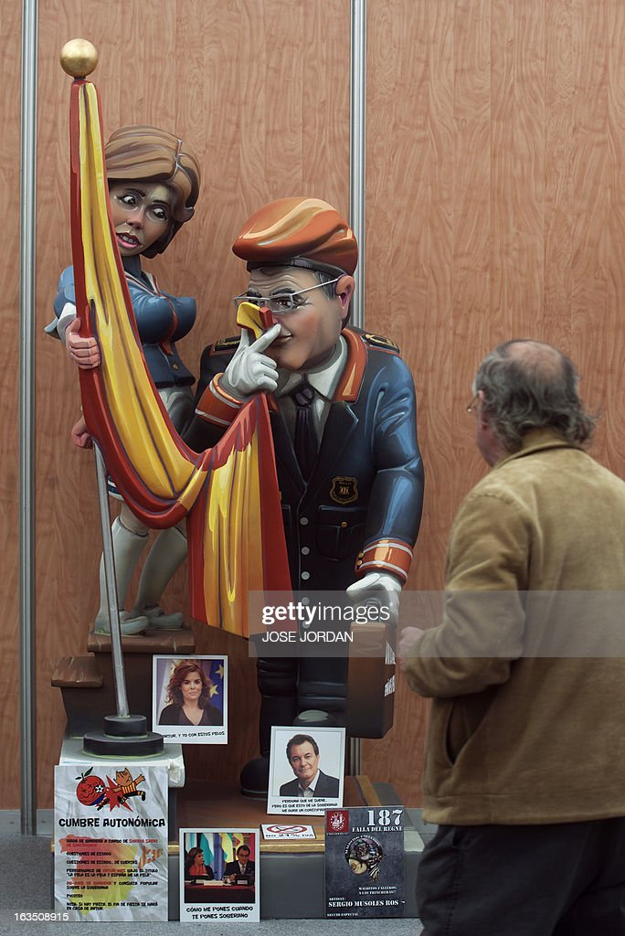 A man looks at a Falla, a gigantic sculpted structure of cardboard and wood which humorously portrays relevant current events and personalities, caricaturing Spain's first deputy prime minister Soraya Saenz de Santamaria and President of the Catalan region Artur Mas, during an exhibition before preparations for the Fallas Festival, in Valencia on March 11, 2013. The Fallas will be burned in the streets of Valencia on March 19, 2013, as a tribute to St. Joseph, patron saint of the carpenters' guild.