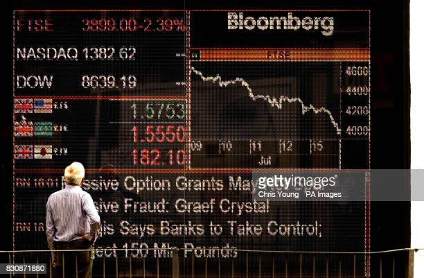 A man looks at a financial Infomation board in a business in west London displaying the steady decline of FTSE index which plunged below 4000 for the...