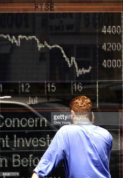 A man looks at a financial Information board in a business in west London displaying the steady decline of FTSE index which plunged Monday below 4000...