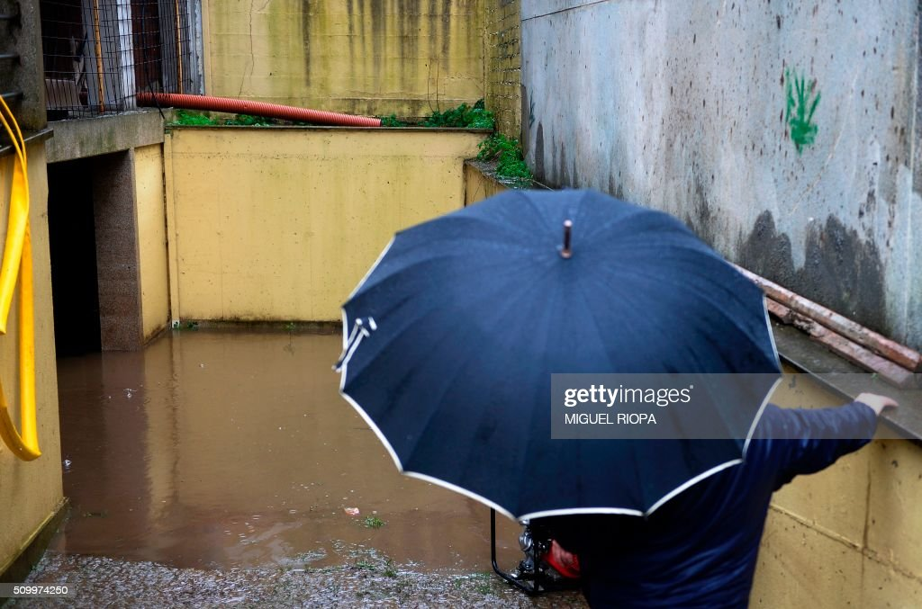 A man looks at a flooded garage after heavy rains in Redondela, northwestern Spain, on February 13, 2016. / AFP / AFP or licensors / MIGUEL RIOPA