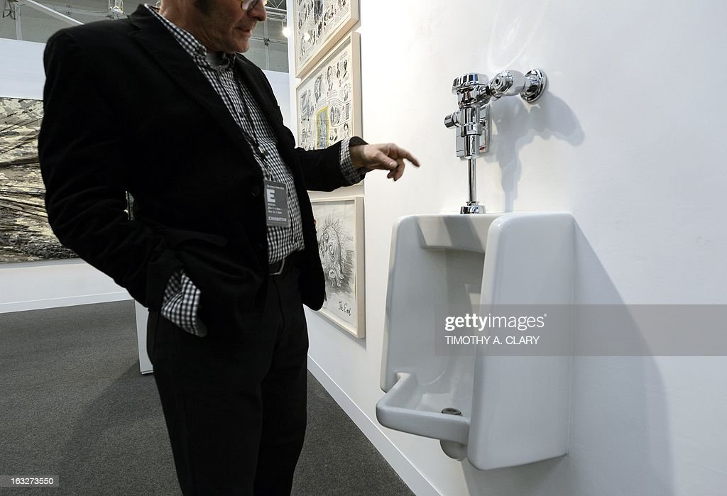 A man looks at a fully functional urinal by artist Andrew Ohanesian titled 'Urinal' during the press preview at the 2013 Armory Show, one of the world's top art events featuring the most influential artworks of the 20th and 21st centuries, at Pier 92 and 94 in New York March 6, 2013. The Armory Show Centennial Edition kicks off Armory Arts Week .