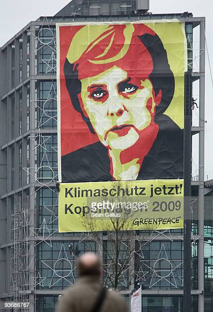 A man looks at a giant banner showing German Chancellor Angela Merkel that reads 'Climate Protection Now Copenhagen 2009' hanging from Hauptbahnhof...