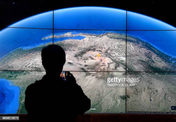 A man looks at a Google Earth map on a screen as Google Earth unveils the revamped version of the application April 18 2017 at a event at New York's...