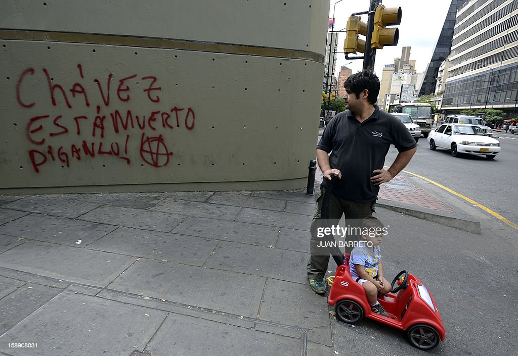 A man looks at a graffiti reading 'Admit it, Chavez is Dead', as he waits to cross an avenue in Caracas, on January 3, 2013. Top Venezuelan officials gathered in Cuba on Thursday amid growing demands for news about cancer-stricken President Hugo Chavez' condition, days before he is to be sworn in for another term. The Venezuelan president has not been seen since he underwent a long and complicated surgery for a recurrence of cancer 23 days ago, and officials have acknowledged that his recovery has been difficult.