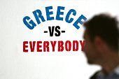 A man looks at a graffiti reading 'Greece vs Everybody' on a wall in central Athens on June 11 2015 The EU's top leaders warned Greek Prime Minister...