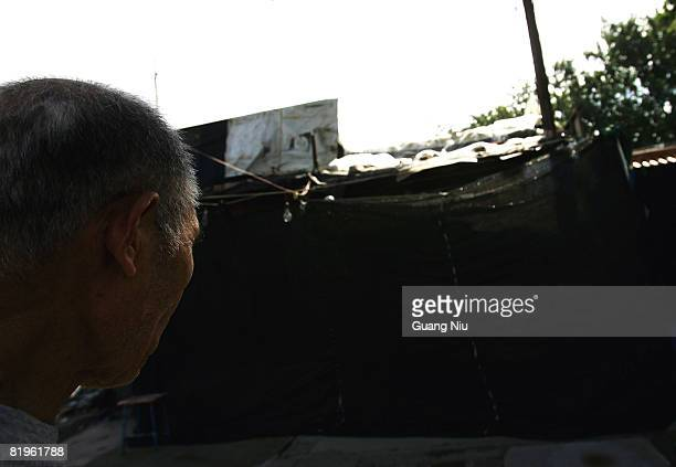 A man looks at a home is covered by Chinese authorities plastered with portraits of China's top communist leaders in an attempt to fight off a...