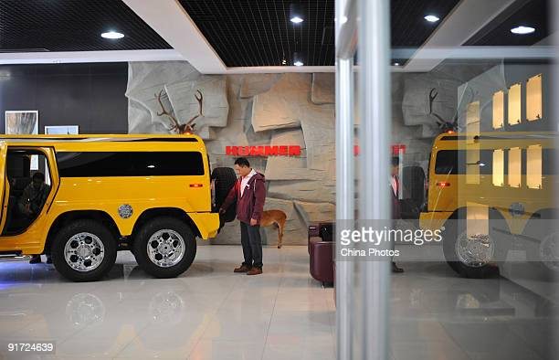 A man looks at a Hummer H2 on display in a Hummer store on October 10 2009 in Chengdu of Sichuan Province China General Motors and Sichuan Tengzhong...