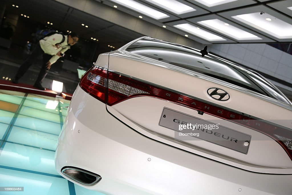 A man looks at a Hyundai Motor Co. 5G Grandeur sedan on display in the showroom at the company's headquarters in Seoul, South Korea, on Tuesday, Jan. 22, 2013. Hyundai Motor Co. is scheduled to release fourth-quarter earnings on Jan. 24. Photographer: SeongJoon Cho/Bloomberg via Getty Images