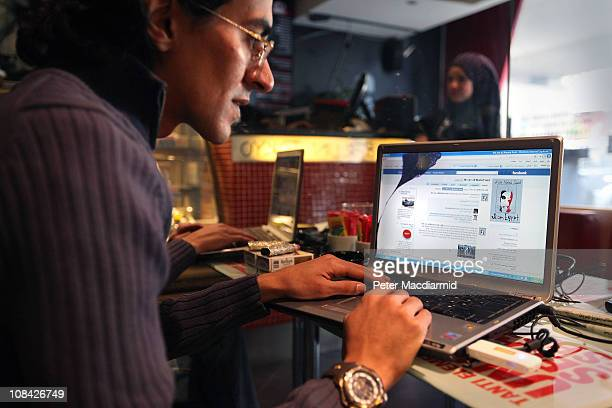 A man looks at a laptop computer displaying Facebook in a cafe on January 27 2011 in Cairo Egypt Thousands of police are on the streets of the...
