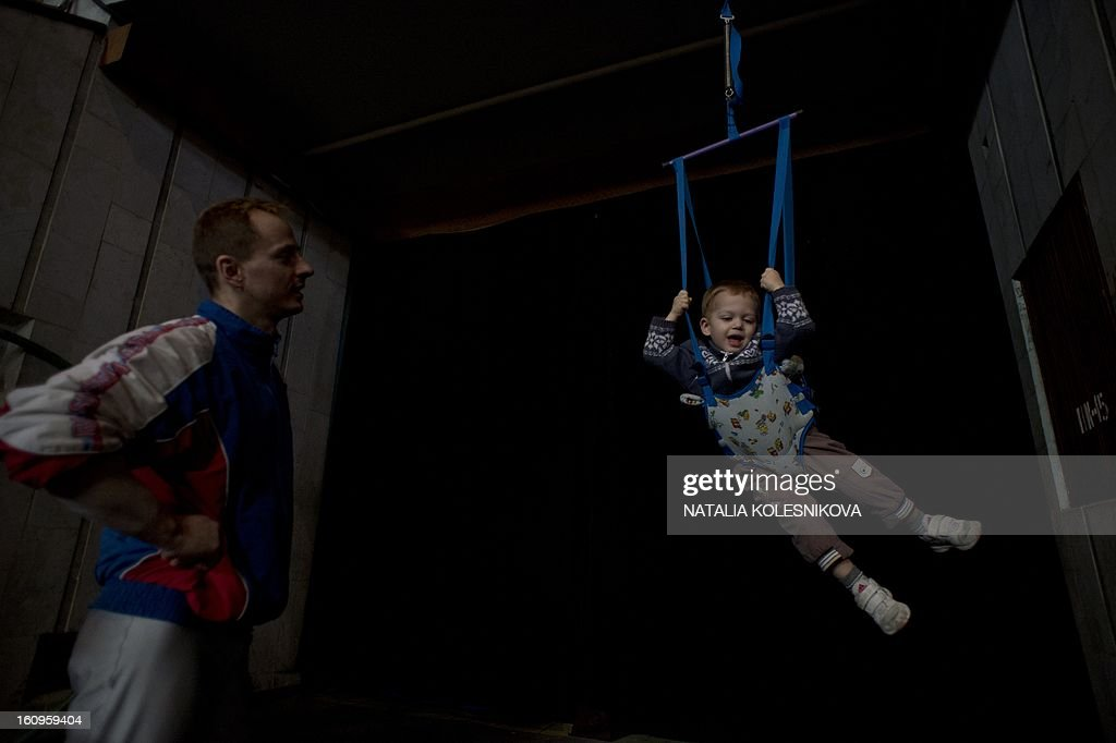 A man looks at a little boy playing acrobat in a circus in the Russian Black Sea resort of Sochi, on February 8, 2013.