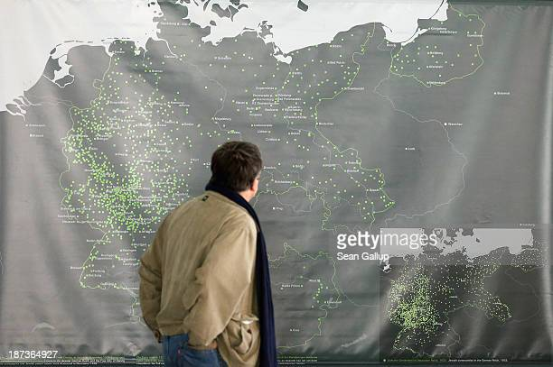 A man looks at a map of the 1930sera German Empire showing cities where Nazi followers burned down synagogues during the 1938 Kristallnacht pogroms...
