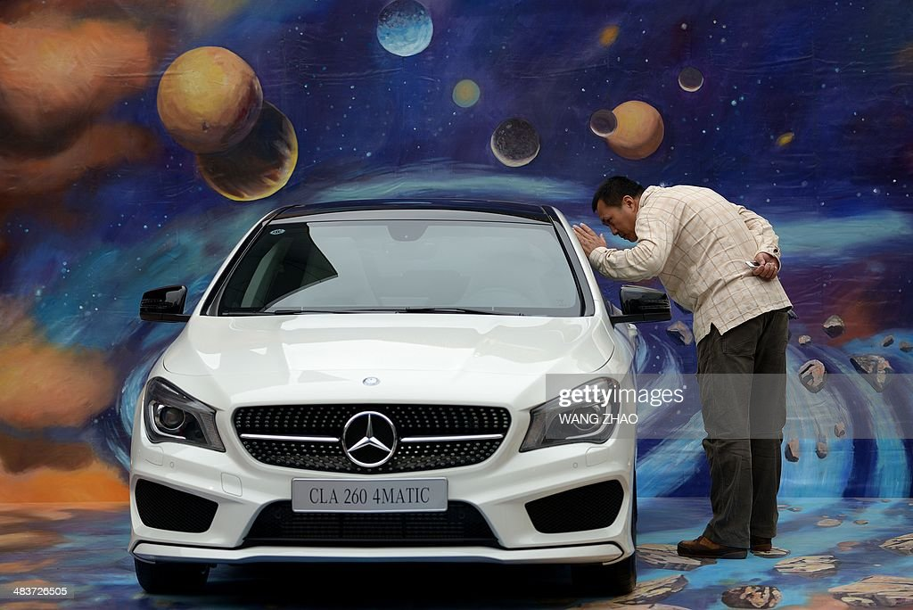 A man looks at a Mercedes Benz car on display in front of a mall in Beijing on April 10 2014 Chinese exports and imports fell sharply in March data...