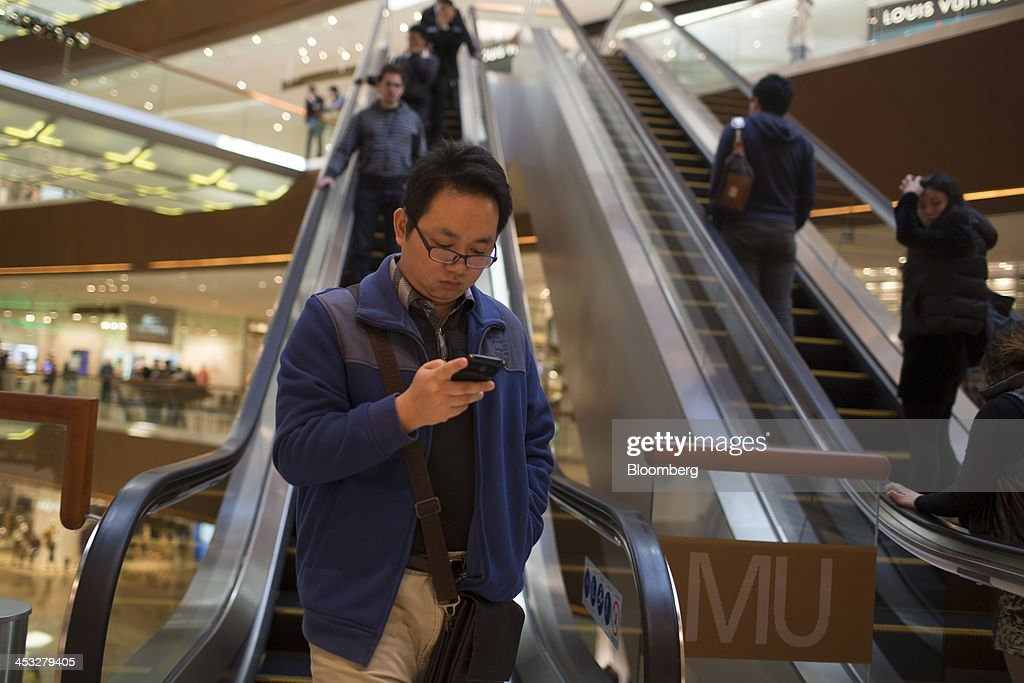 A man looks at a mobile phone while exiting an escalator inside the TaiKoo Hui shopping mall, operated by Swire Properties Ltd., in Guangzhou, China, on Saturday, Nov. 30, 2013. China's government may set its 2014 growth target at 7 percent, the Economic Information Daily reported on Dec. 3, citing the State Information Center. This compares with a goal of 7.5 percent for this year. Photographer: Brent Lewin/Bloomberg via Getty Images