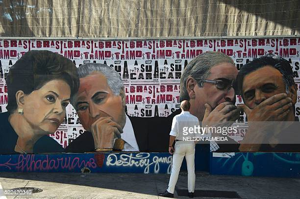 A man looks at a mural depicting the president of the Brazilian lower house of Congress Eduardo Cunha speaking with the president of the Brazilian...