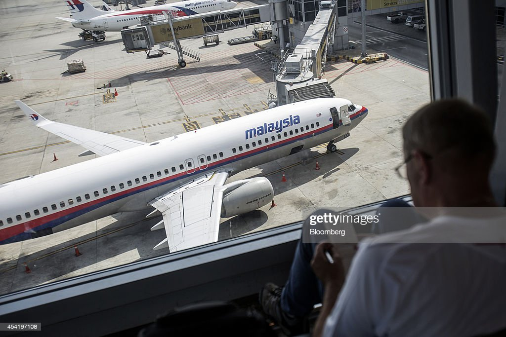 A man looks at a notepad as an aircraft operated by Malaysian Airline System Bhd. (MAS) stands on the tarmac at Kuala Lumpur International Airport (KLIA) in Sepang, Malaysia, on Tuesday, Aug. 26, 2014. Malaysia Airlines are scheduled to release second quarter earnings Aug. 27 as the airline considers job cuts, a review of aircraft orders and replacing its chief executive officer after the national carrier suffered two disasters this year, people familiar with the plan said. Photographer: Charles Pertwee/Bloomberg via Getty Images