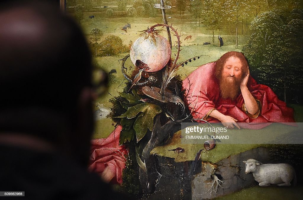 A man looks at a painting at the 'Hieronymus Bosch, Visions of a Genius' exhibition during a press preview at the Noordbrabants Museum in Den Bosch on February 11, 2016. To mark the 500th anniversary of Dutch painter Hieronymus Bosch's death, a small museum in his hometown has managed to bring most of the last 25 known surviving paintings by the man dubbed 'the devil's painter' for a major exhibition of his work scheduled from February 13 to May 8, 2016. / AFP / EMMANUEL DUNAND
