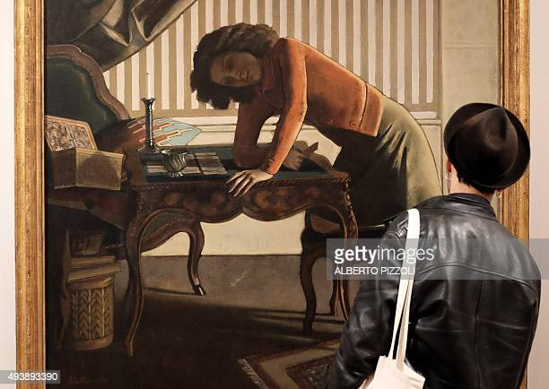 A man looks at a painting by late French artist Balthus as he visits the exhibition dedicated to his work at the Villa Medici in Rome on October 23...