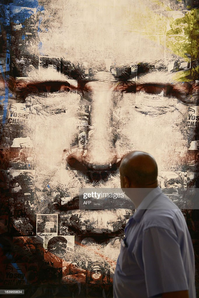 A man looks at a picture of the late Venezuelan President Hugo Chavez at an exhibit near his remains at the 'Quarter of the Mountain' in the 23 de Enero Chavez bastion, in Caracas, on March 18, 2013. The 'Quarter of the Mountain', where the body of Chavez lies, while deciding on its transfer to the National Pantheon, is a former barracks that was the center of operations of the failed coup led by Chavez on February 4, 1992.