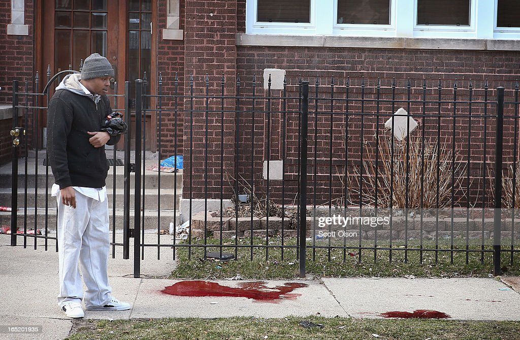 A man looks at a pool of blood on the sidewalk where a 24-year-old man was shot and killed on South Eberhart Avenue on the city's South Side April 1, 2013 in Chicago, Illinois. According to published reports, the man was the 73rd homicide victim and the 39th victim under the age of 25 in Chicago in 2013.