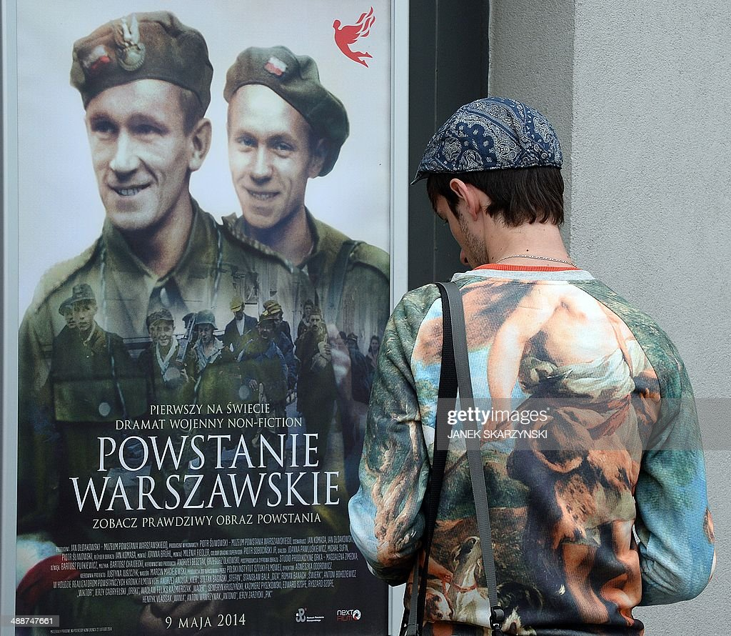 A man looks at a poster for 'Warsaw Rising', a unique feature film that has added color, sound and a story line to original black-and-white film clips recorded by cameramen for the rebel Polish Home Army during its doomed 1944 revolt against Nazi German forces occupying the Polish capital during World War II on May 8, 2014 in Warsaw. The movie opens in cinemas across Poland on Friday.