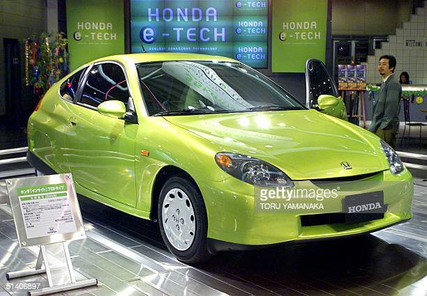 A man looks at a prototype of Honda's new hybrid car 'Insight' which will be on sale from this autumn at Honda headquarters in Tokyo 06 July 1999 The...