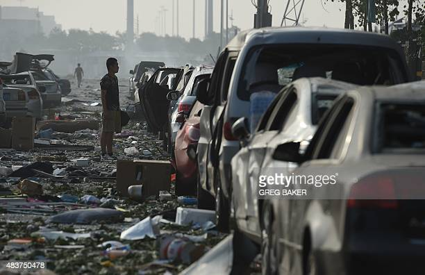 A man looks at a row of damaged cars outside a residential building near the site of a series of explosions in Tianjin northern China on August 13...