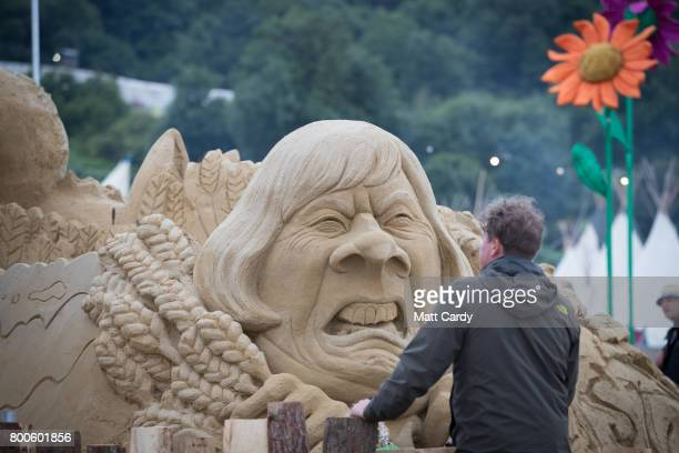 A man looks at a sand sculpture of Prime Minister Theresa May at the Glastonbury Festival site at Worthy Farm in Pilton on June 24 2017 near...
