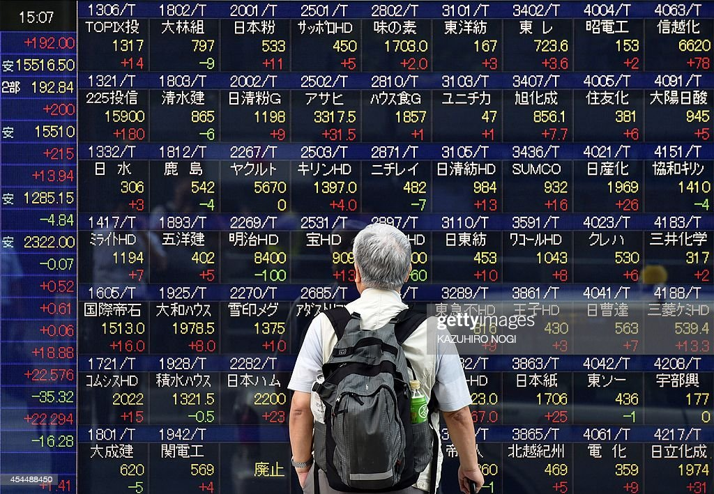 A man looks at a share price board of the Tokyo Stock Exchange in Tokyo on September 2 2014 Tokyo stocks closed at their highest level in over seven...