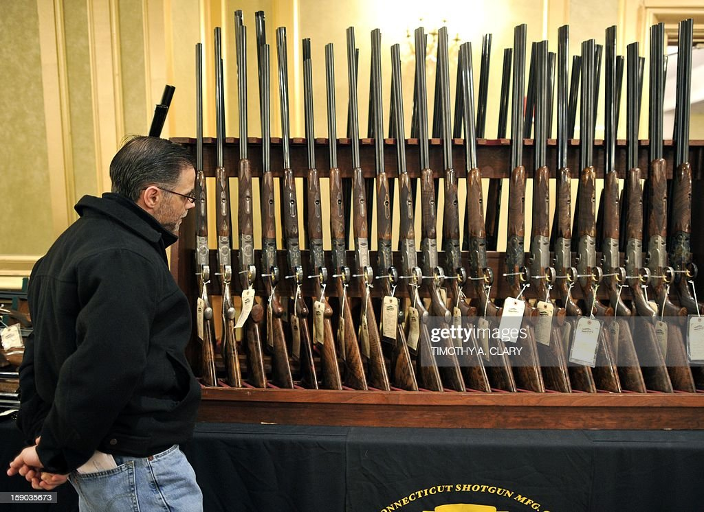 A man looks at a shotguns during the 8th Annual East Coast Fine Arms Show in Stamford, Connecticut January 6, 2013. This is the first gun show in Connecticut sine the December 14 shooting that killed 20 children and six teachers from Sandy Hook Elementary School approximatley 40 miles away in Newtown, Ct. The gun show featured collectible and antique weapons.