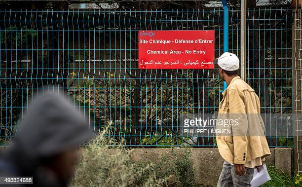 A man looks at a sign on a fence protecting a chemical plant regulated by the Seveso directive on October 19 near the 'New Jungle' migrants camp in...