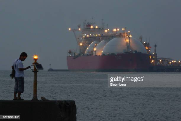 A man looks at a smartphone while standing across from a liquefied natural gas tanker berthed at Tokyo Electric Power Co's Futtsu gasfired thermal...
