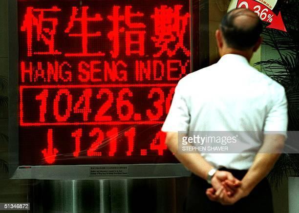 A man looks at a streetside sign displaying Hong Kong's closing stock numbers for 23 October Hong Kong's key Hang Seng index plunged 104 percent to...