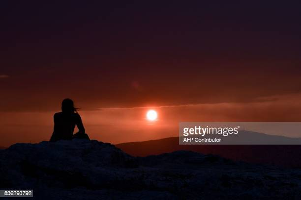 A man looks at a sunset on Filipappou hill in Athens as heavy rain cloud hang over the city on August 21 2017 / AFP PHOTO / LOUISA GOULIAMAKI
