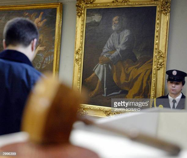 A man looks at a 'The Tears of San Pedro' painting by Spanish artist Diego Velazquez during an auction in Madrid 19 February 2004 AFP PHOTO/ Javier...