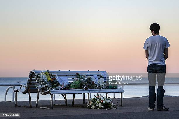 A man looks at a tribute laying on a bench near where a person was killed on the Promenade des Anglais on July 17 2016 in Nice France Six people...