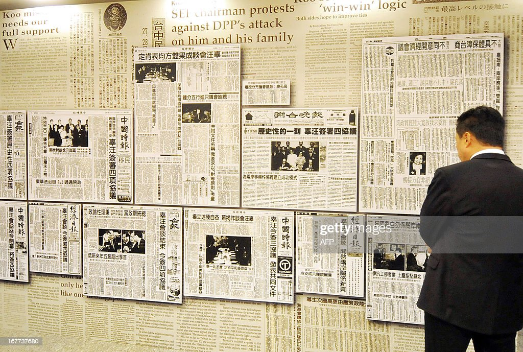 A man looks at a wall of enlarged paper clippings featuring the historic 1993 Taiwan-China peace talks at the headquarters of the island's quasi-official Straits Exchange Foundation in Taipei on April 29, 2013. Taiwan's President Ma Ying-jeou renewed the 'one China' policy of his government as Taiwan marked the 20th anniversary of the of the first high-level talks between Taiwan and the Chinese mainland since their split in 1949 at the end of a civil war. AFP PHOTO / Mandy CHENG