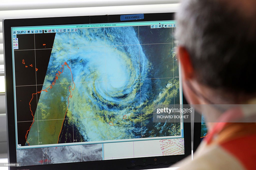 A man looks at a weather map, on January 2, 2013 at Meteo France local headquarters in Saint-Denis de la Reunion, a French island located in the Indian Ocean, as tropical storm Dumile is forecast to strike the island as a tropical cyclone later today.