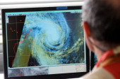 A man looks at a weather map on January 2 2013 at Meteo France local headquarters in SaintDenis de la Reunion a French island located in the Indian...