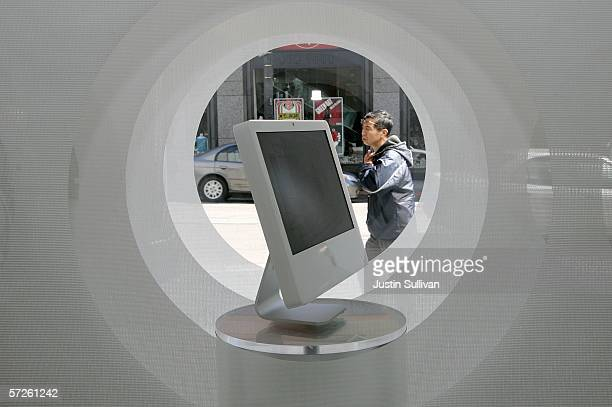 A man looks at a window display featuring an Apple iMac computer at an Apple Store April 5 2006 in San Francisco Apple Computer Inc unveiled 'Boot...