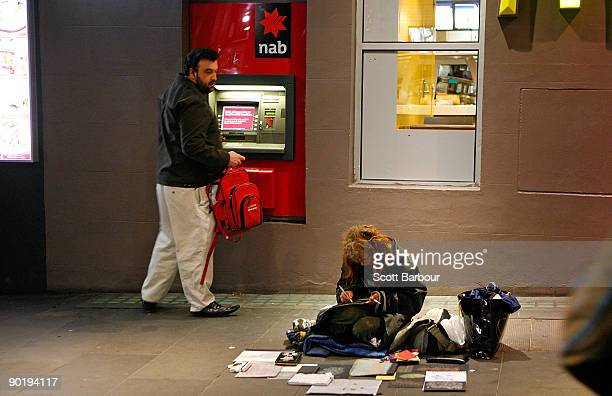 A man looks at a woman sitting on the pavement as he withdraws money from an ATM machine during the �Hands Up for the Homeless� campaign on August 31...