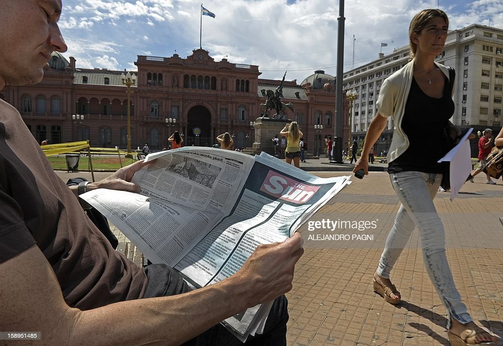 A man looks at an advert placed by Britain's biggest-selling tabloid The Sun in the Buenos Aires Herald warning Argentina to keep its 'hands off' the Falklands, at Mayo Square in front of the presidential palace Casa Rosada in Buenos Aires, on January 4, 2013. The Sun hit back at Argentina's President Cristina Fernandez de Kirchner's renewed claim over the disputed Falkland Islands in an open letter to her in the Buenos Aires Herald newspaper on Friday, a day after Fernandez de Kirchner published her own open letter in two British newspapers urging Britain to give up the South Atlantic islands. AFP PHOTO/ALEJANDRO PAGNI