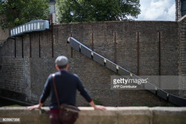 A man looks at an artwork entitled 'Paysage glisse' by Tact Architects and Tangui Robert on the Castle of Nantes on June 29 2017 during the 6th...