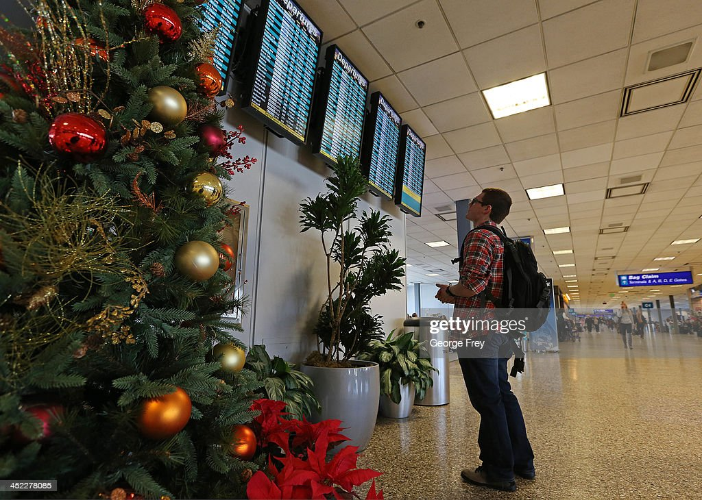 A man looks at an departure board at the Salt Lake City international Airport on November 27, 2013 in Salt Lake City, Utah. A wintry storm system that is covering much of the nation is threatening to wreak havoc on holiday travel .