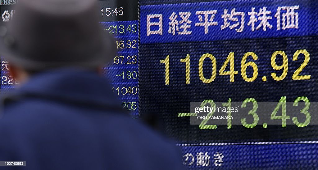A man looks at an electric quotation board flashing the Nikkei key index of the Tokyo Stock Exchange (TSE) in front of a securities company in Tokyo on February 5, 2013. Tokyo stocks closed 1.90 percent lower on February 5 as political concerns in Spain and Italy put the eurozone's long-running debt crisis back on to the radar. AFP PHOTO/Toru YAMANAKA
