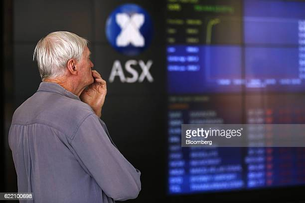 A man looks at an electronic board displaying stock information inside the Australian Securities Exchange operated by ASX Ltd in Sydney Australia on...