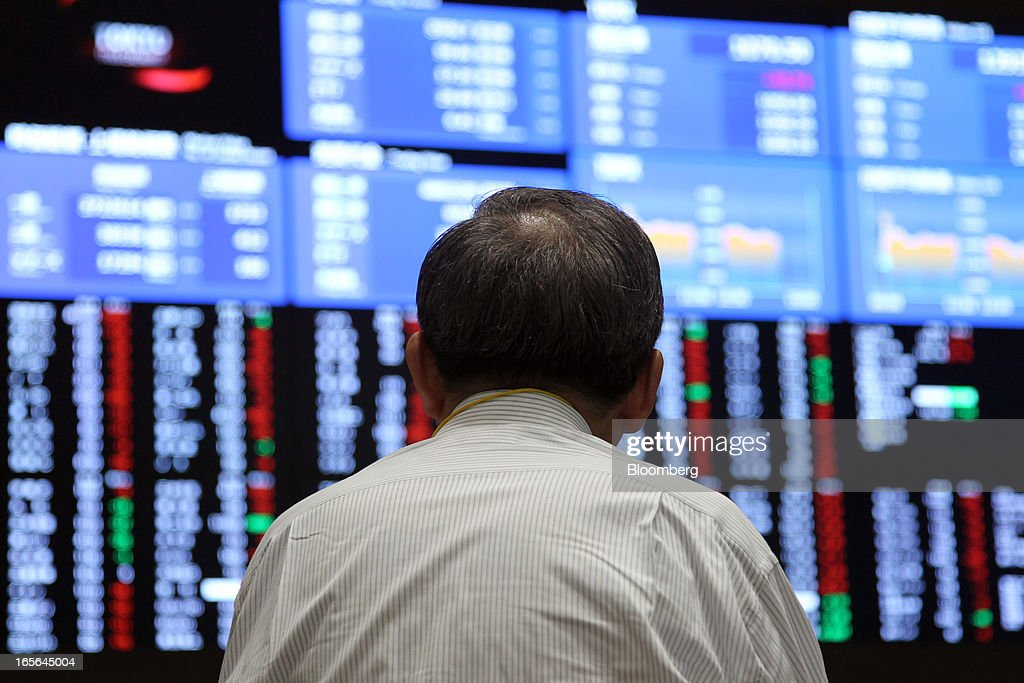 A man looks at an electronic board displaying stock prices at the Tokyo Stock Exchange in Tokyo, Japan, on Friday, April 5, 2013. Japanese stocks surged, with the Nikkei 225 Stock Average capping the biggest three-day rally in two years, after Haruhiko Kuroda announced unprecedented stimulus in his first policy meeting as Bank of Japan governor. Photographer: Junko Kimura/Bloomberg via Getty Images
