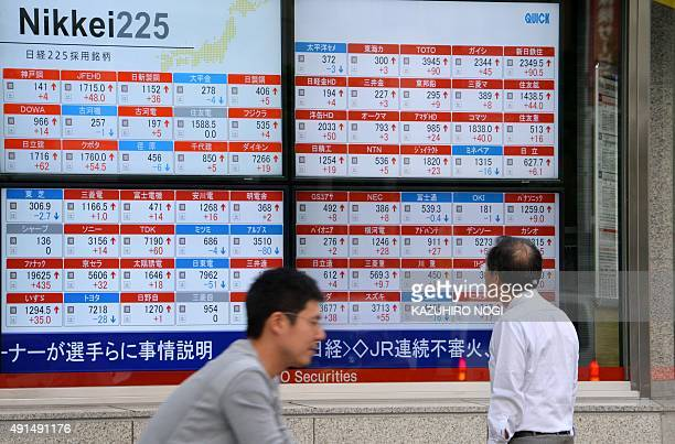A man looks at an electronic board showing movement of the Nikkei 225 at the Tokyo Stock Exchange in Tokyo on October 6 2015 Tokyo stocks ended up 10...