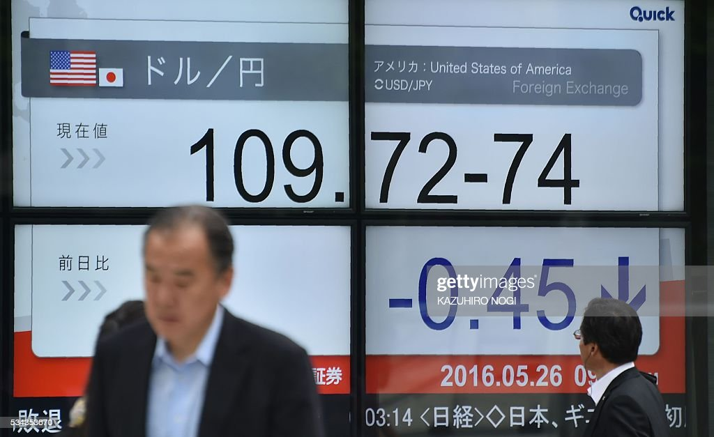 A man (R) looks at an electronic display showing the foreign exchange rate against the US dollar in Tokyo on May 26, 2016. Tokyo shares opened sharply higher on May 26, building on the previous day's gains driven by rising oil prices, with markets eyeing the start of a Group of Seven leaders' summit in Japan. / AFP / KAZUHIRO