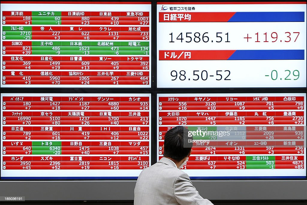A man looks at an electronic stock board displaying the closing figure of the Nikkei 225 Stock Average, top right, in Tokyo, Japan, on Thursday, Oct. 17, 2013. Japanese shares rose, with the Topix index climbing to a three-week high, after the U.S. Congress voted to end the government shutdown and raise the debt ceiling, ending the nation's fiscal impasse. Photographer: Kiyoshi Ota/Bloomberg via Getty Images