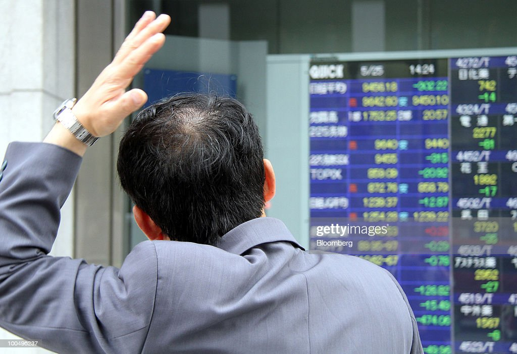 A man looks at an electronic stock board outside a securities firm in Tokyo, Japan, on Tuesday, May 25, 2010. Japanese stocks fell, dragging the Nikkei 225 Stock Average to its lowest close in almost six months on growing signs European financial institutions are facing stress and as the yen rose against the euro and dollar. Photographer: Haruyoshi Yamaguchi/Bloomberg via Getty Images